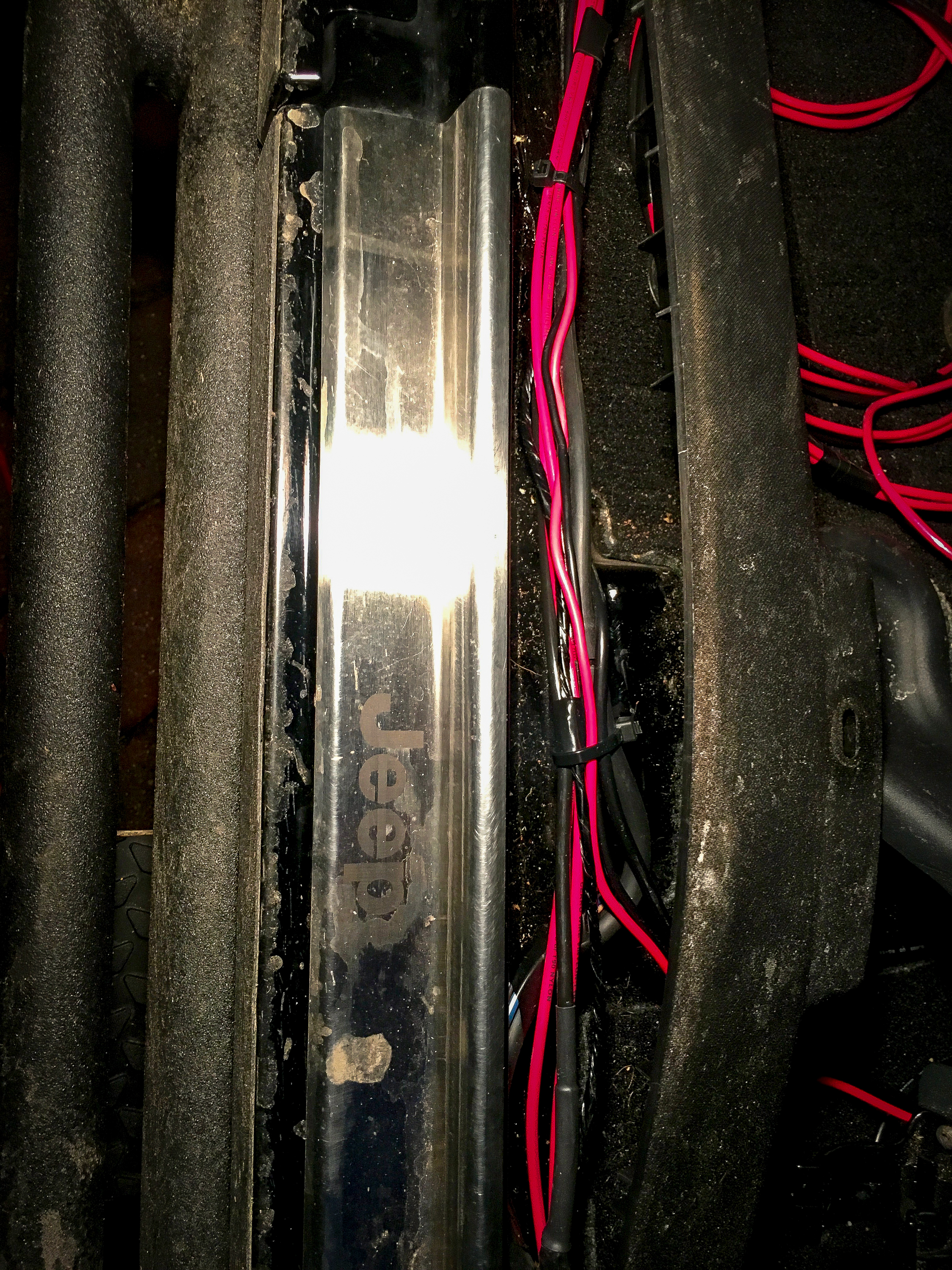 I pulled the plastic trim pieces between the doors at the bottom, as well as the plastic trim along the inside rocker panels. Here I am following Jeeps wiring harness...