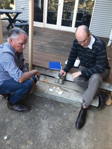 - Photo: David Habel and Andrew Stevens discussing the colour of the mortar mix used in the repairs.