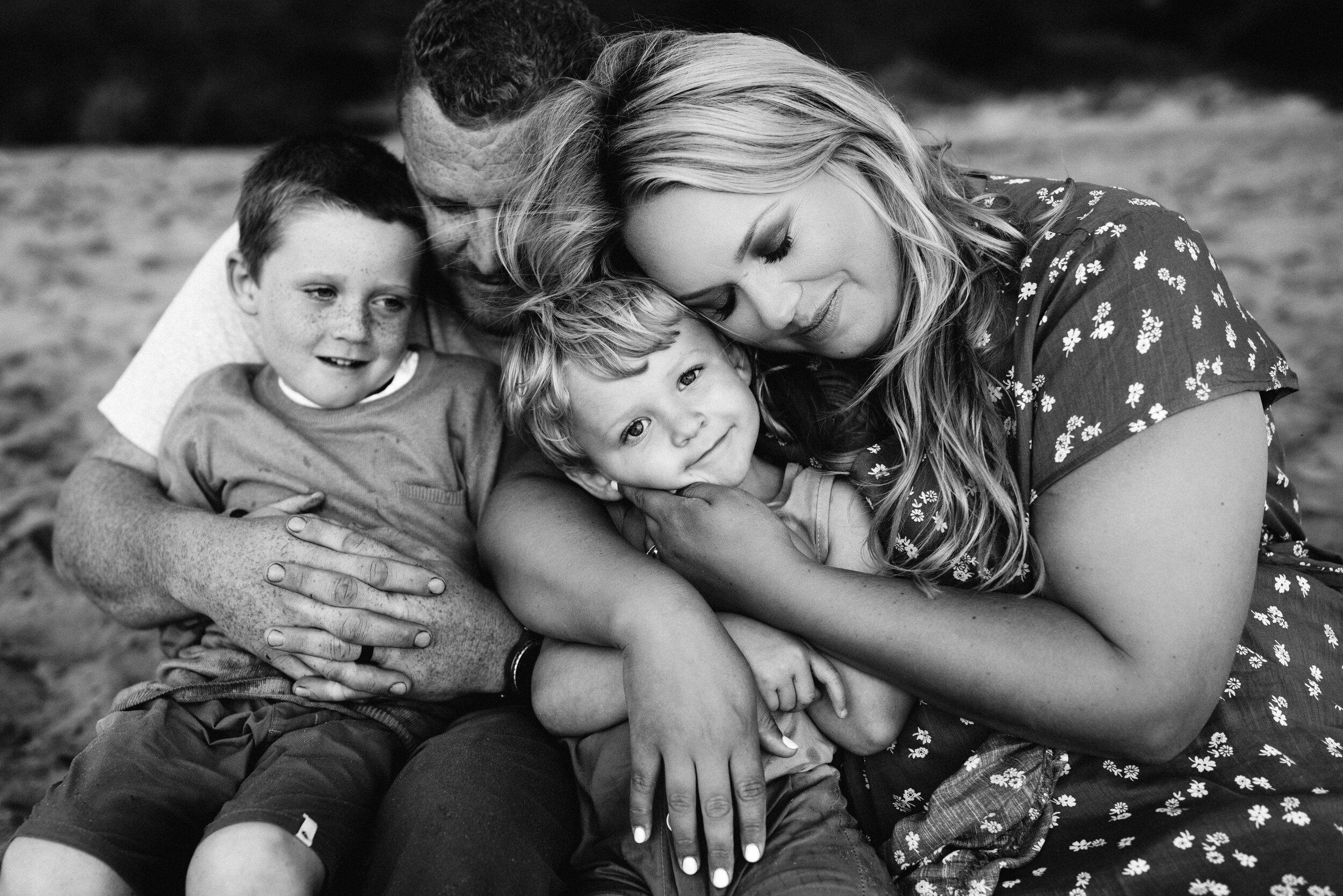 family cuddles on beach photoshoot