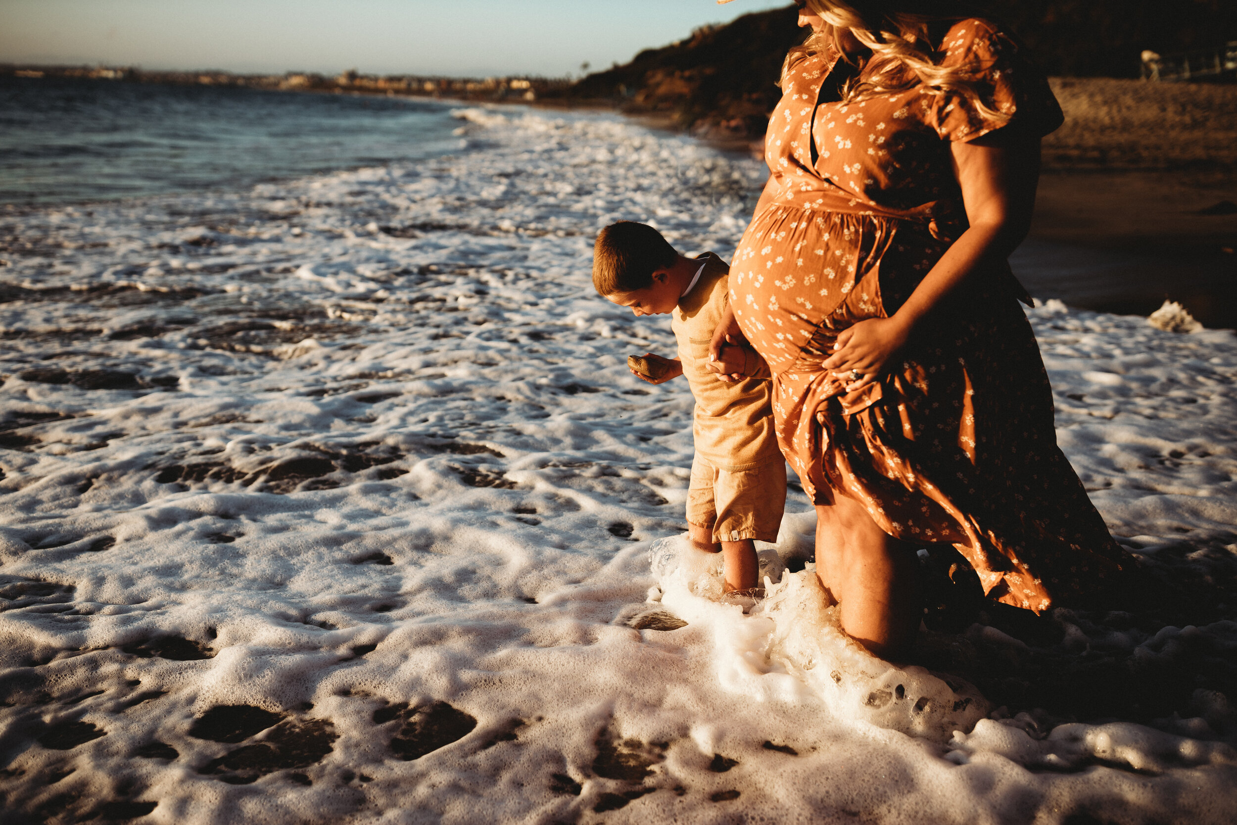 mother and son in crashing waves during photoshoot