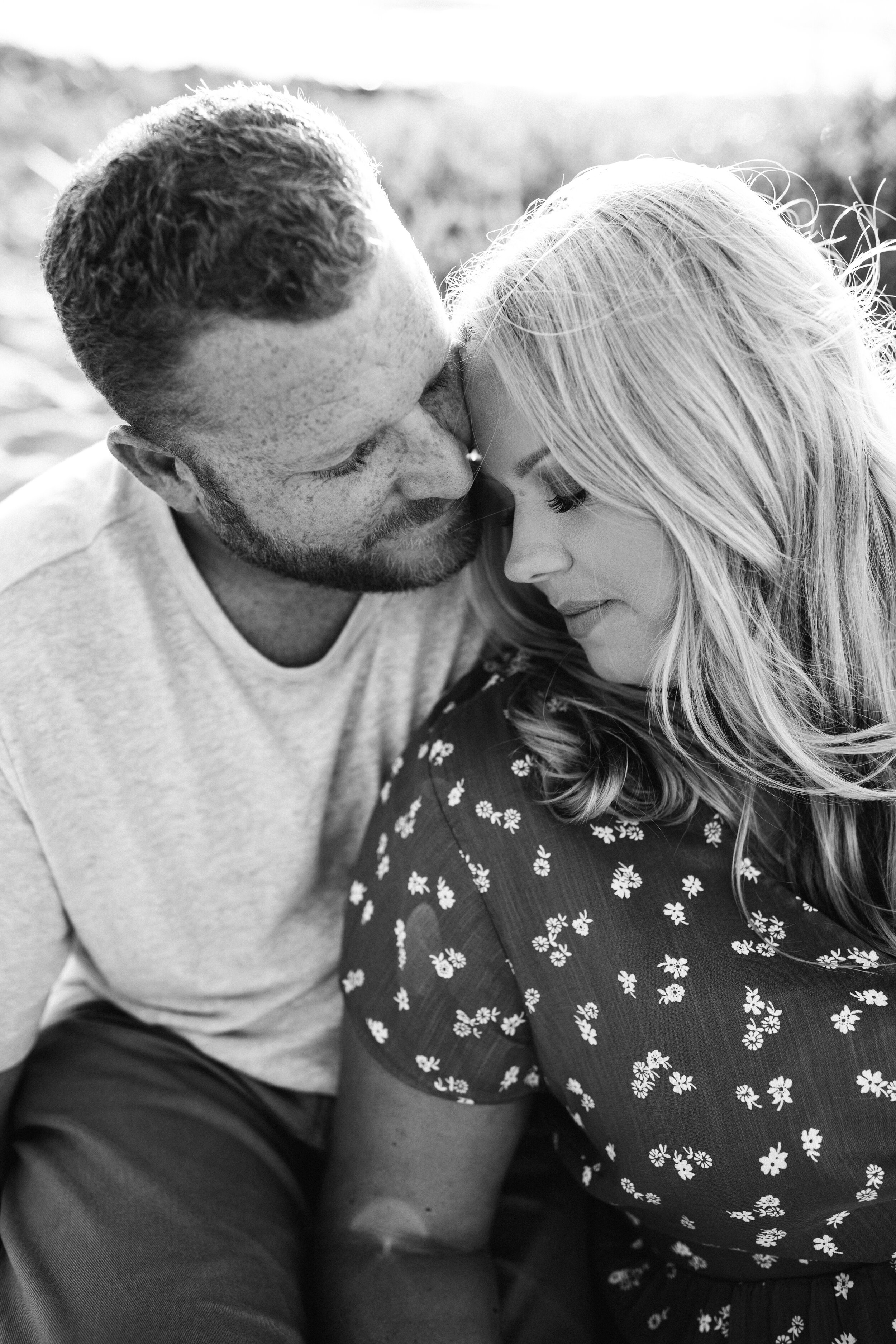 mother and father cuddling on beach - Lindsay Petty Photography
