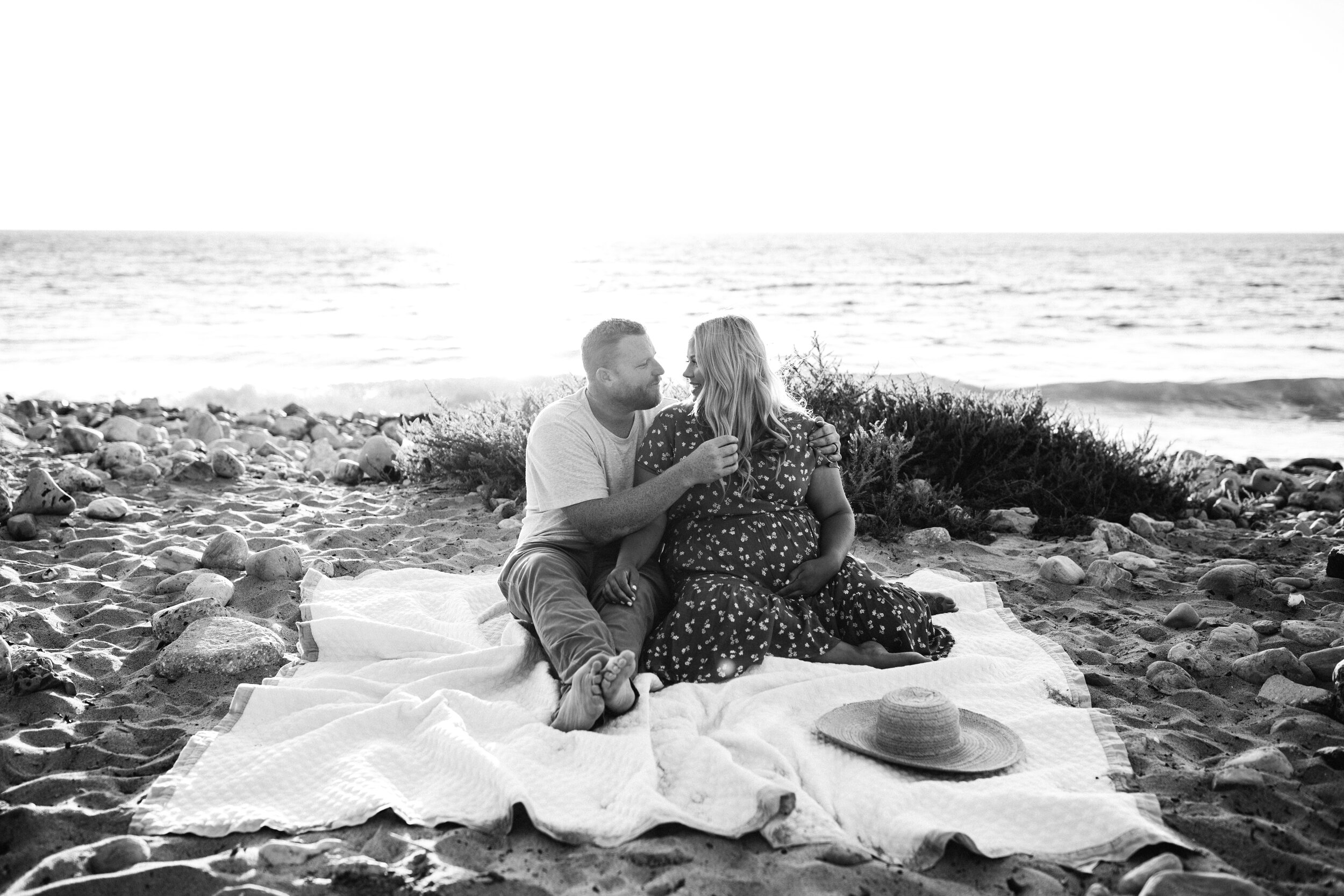 mom and dad cuddling on beach - Lindsay Petty Photography