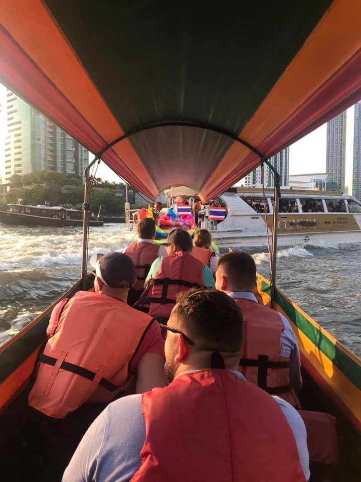 Group of good folks from Ukraine enjoying a long tail boat on the Chao Praya River at the start of a khlong (canal) tour.