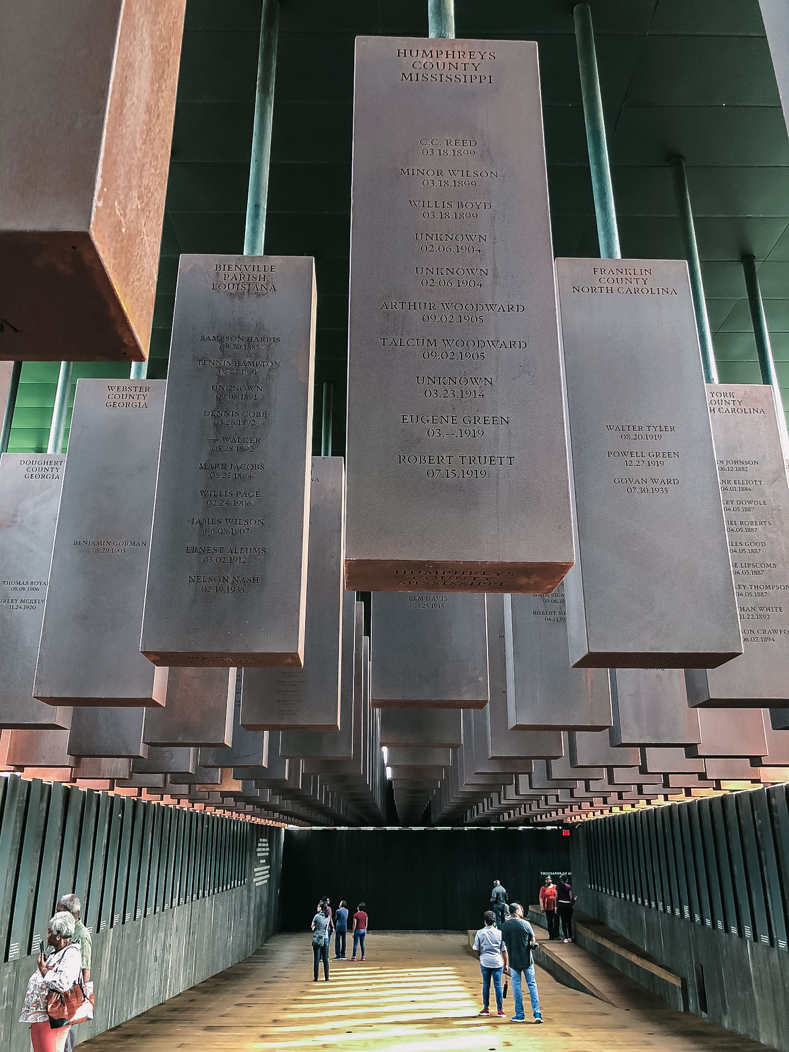 Upon entering the space, the steel monuments are installed on the ground. As you walk further downhill though the space, the memorials hang above you, a chilling reminder of the inhumane racial terror lynchings of more than 4,000 African American men and women.
