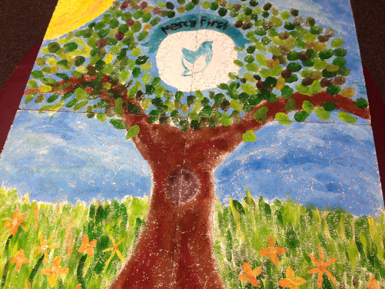 Painting of a tree with MercyFirst's logo, two birds