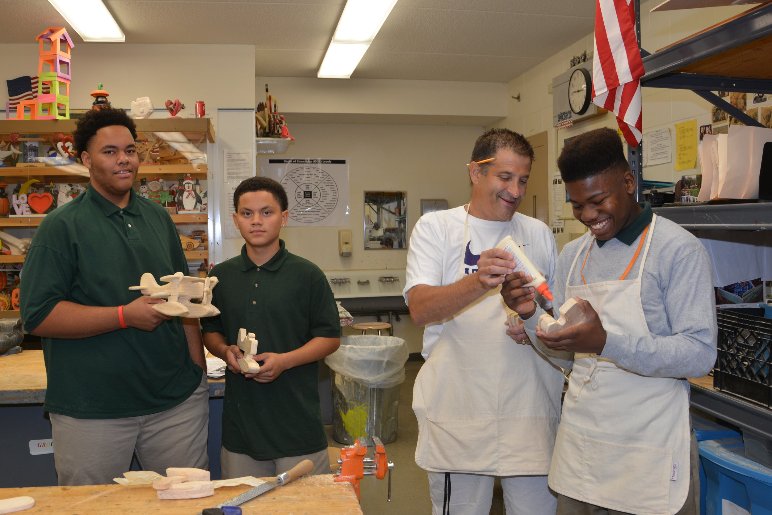 Three students in the wood shop with a teacher
