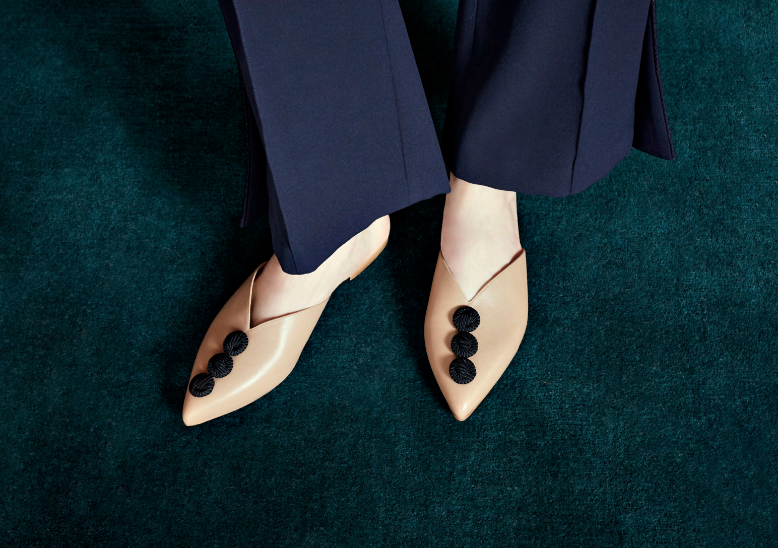 The Maya: Tan leather flat mule with decorative silk buttons. Coming soon.