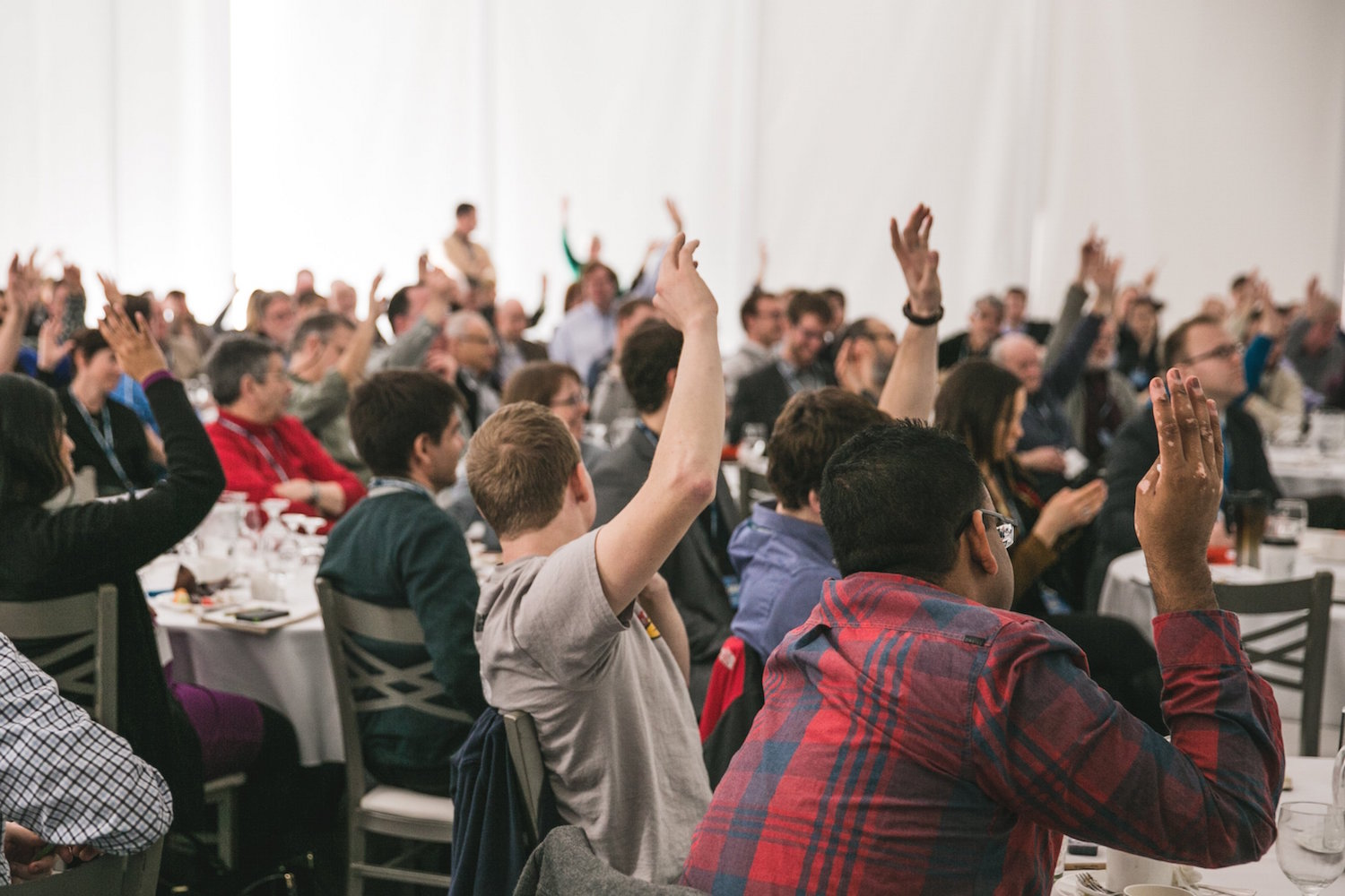 People raising their hands during a meeting.