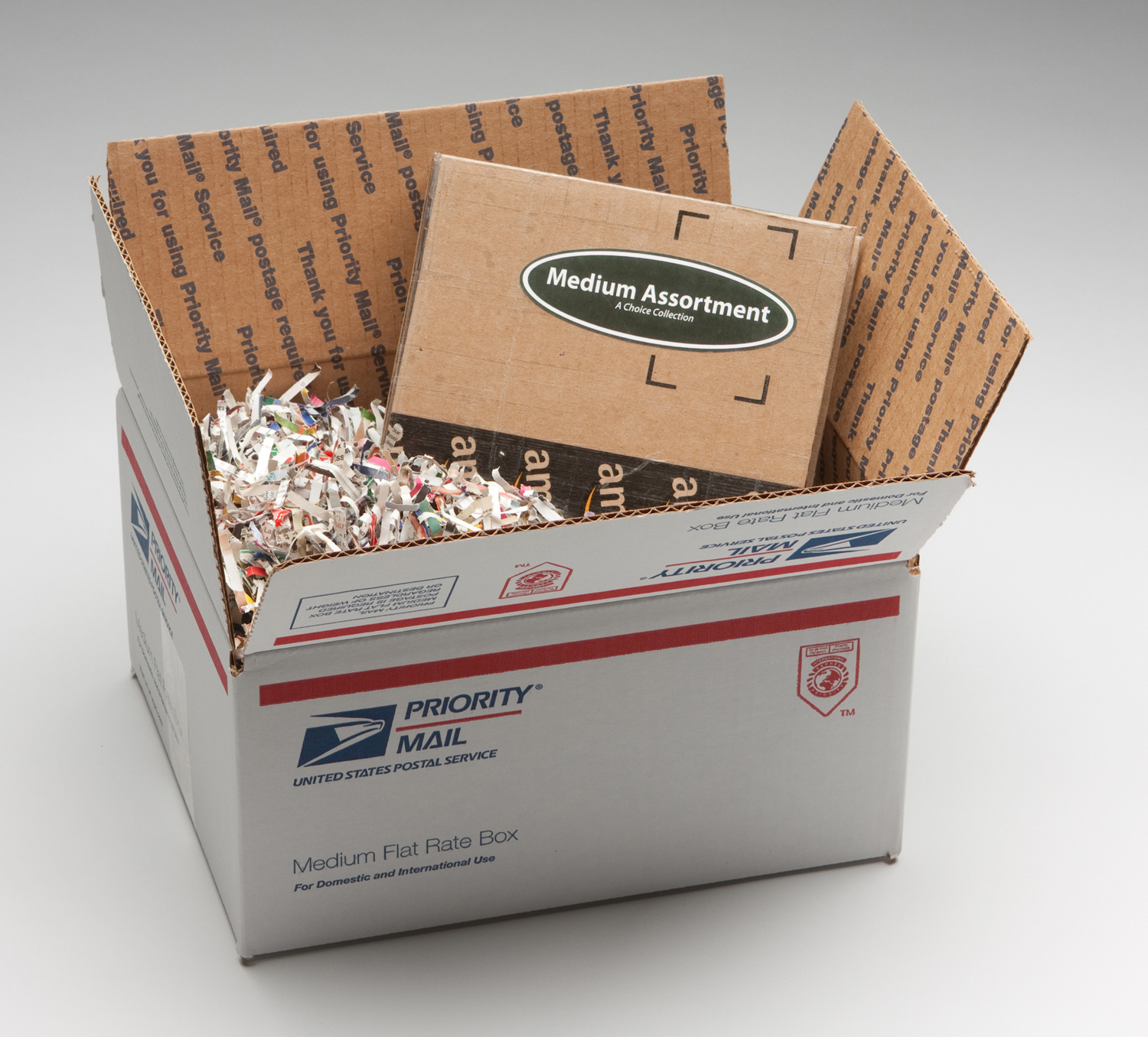The clamshell in the shipping container, packed in shredded mail order catalogs.