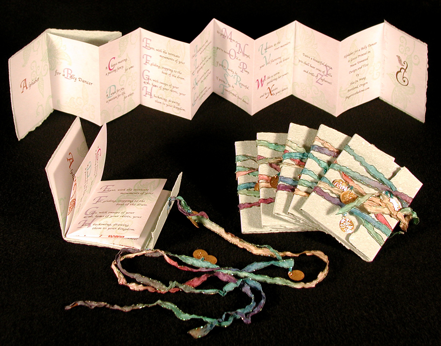 Image shows multiple copies of the book, closed & opened.