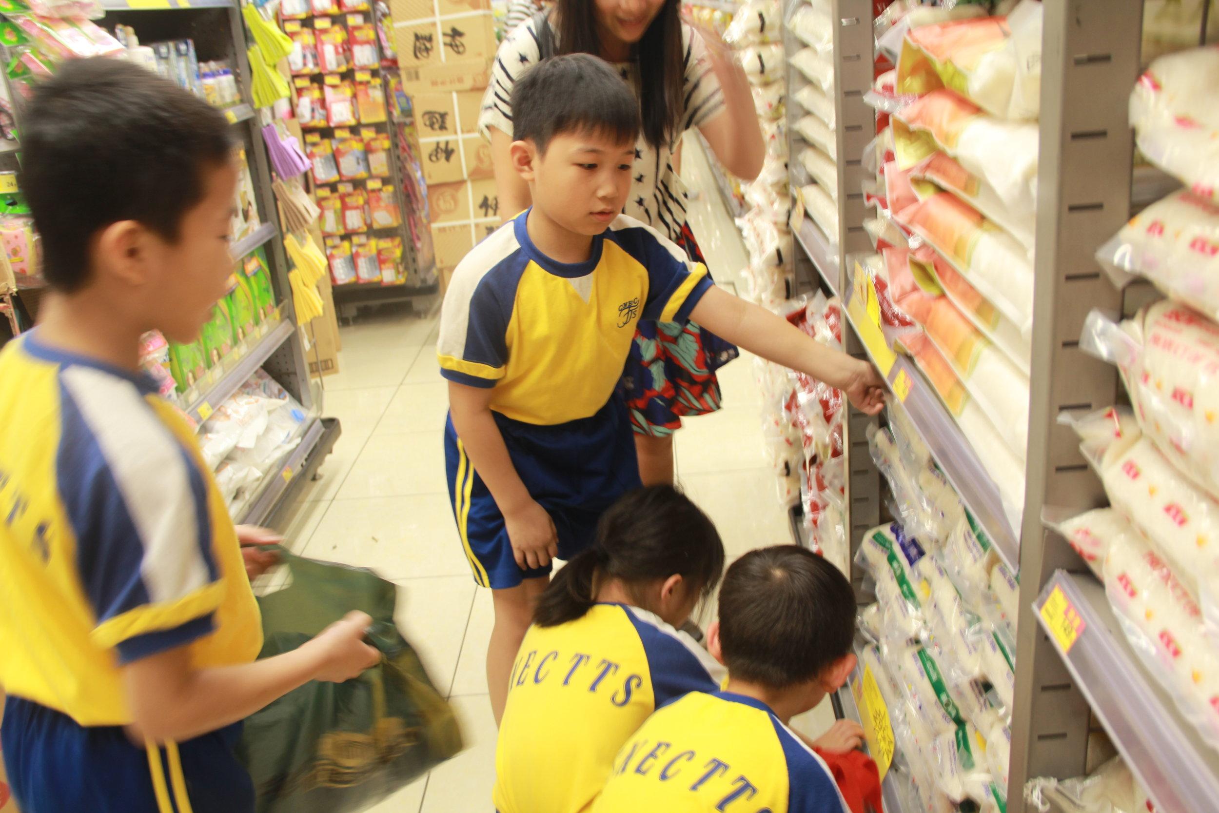 同學們仔細地閱讀不同的標價牌。