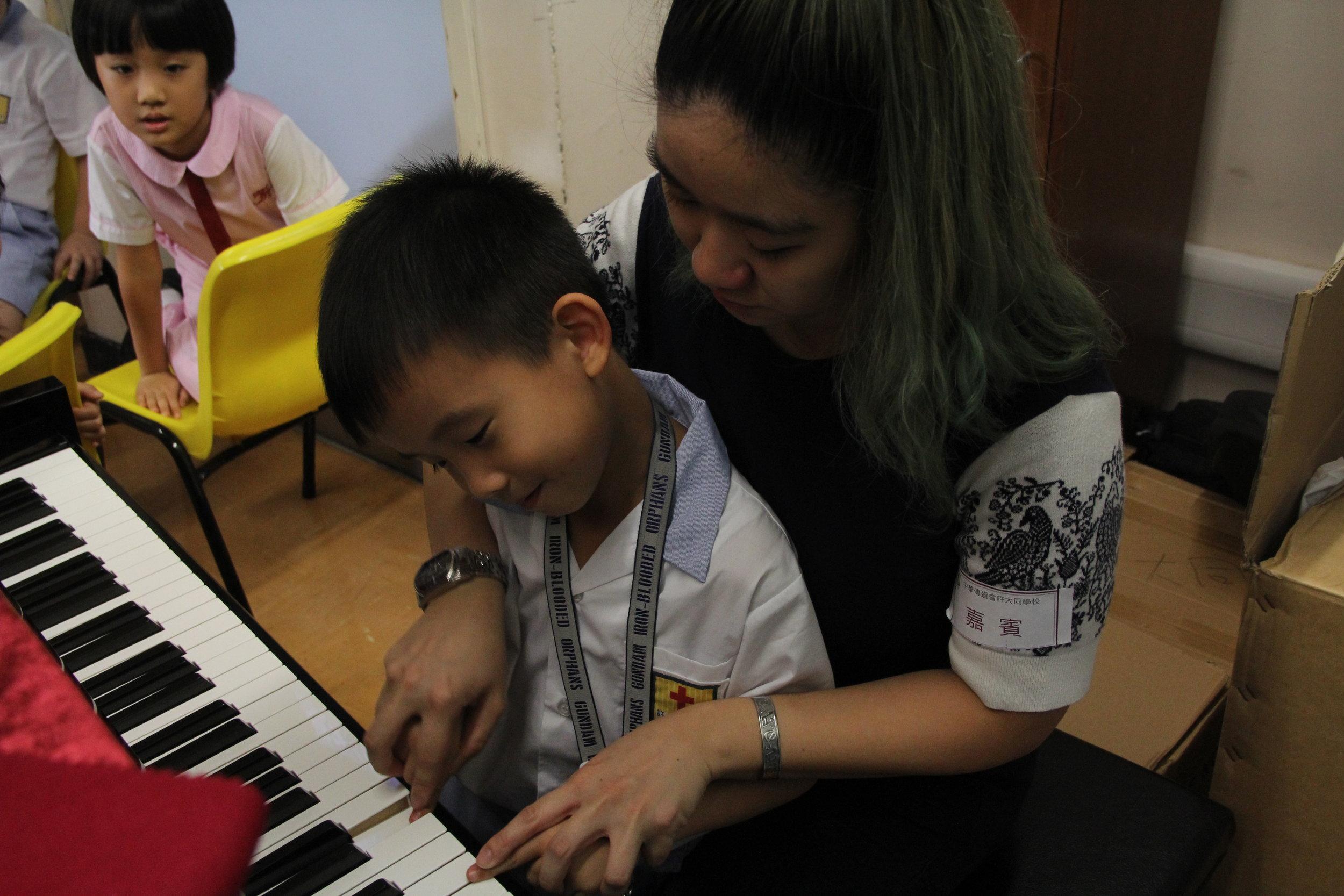 導師教導同學彈奏鋼琴,同學陶醉於美妙的琴聲中!
