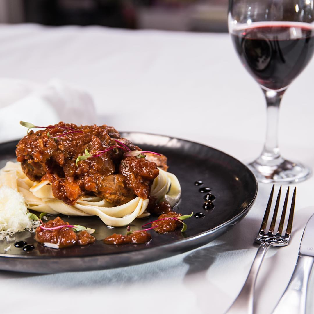 Peter Ansell's slow cooked lamb in a luxury tomato and red wine reduction served on pasta with a glass of red wine