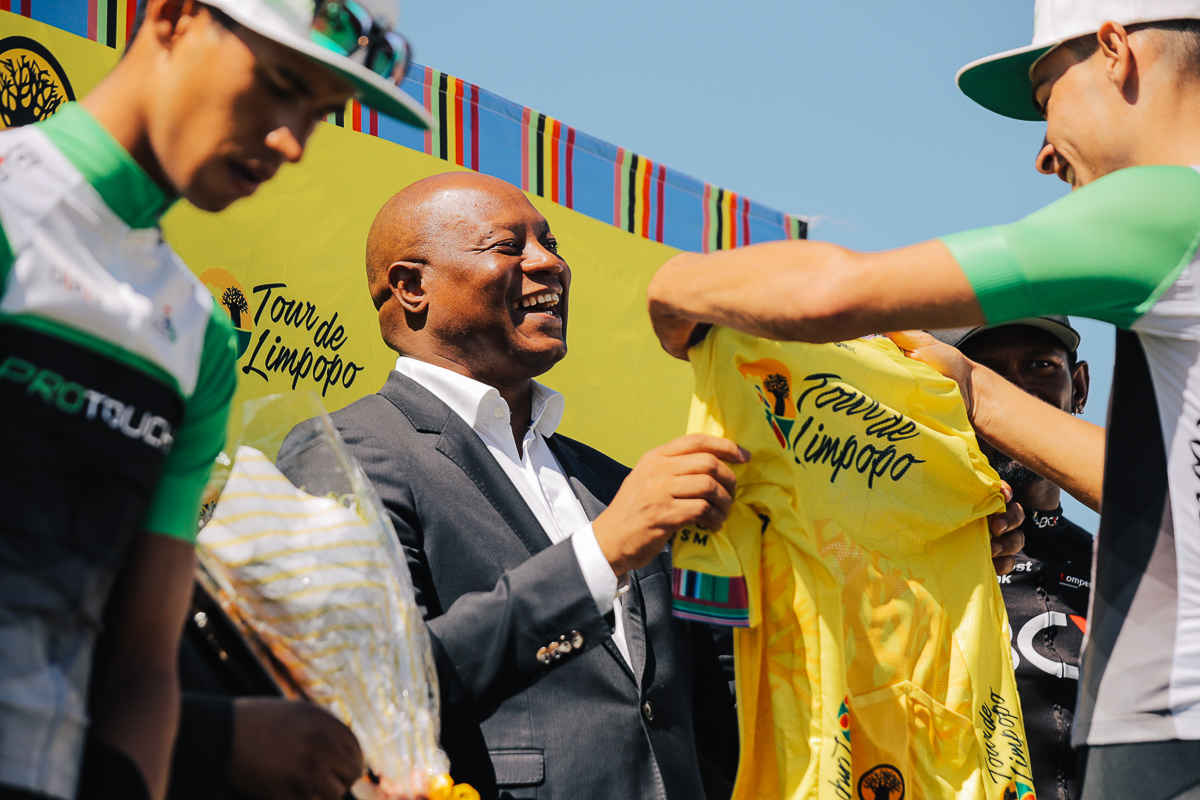 MEC Hon Seaparo Sekoati shares a joke with overall race winner Gustav Basson (ProTouch Sports) as he is awarded the yellow jersey, while teammate Jayde Julius and Clint Hendricks (Team BCX) look on, on Stage 4 of the Tour de Limpopo from Tzaneen to Polokwane on Thursday 26 April 2018 © HaydsBrown