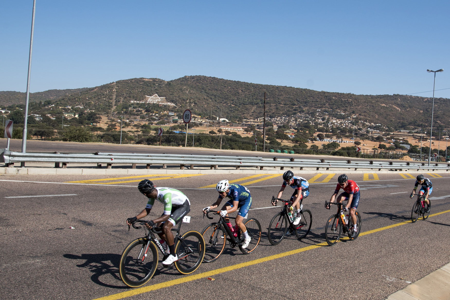 The lead group of riders pass Zionist City Moria from Polokwane to Tzaneen on Stage 2 of the 2019 Tour de Limpopo (UCI 2.2) from 14-18 May © Tour de Limpopo/Andrew Mc Fadden
