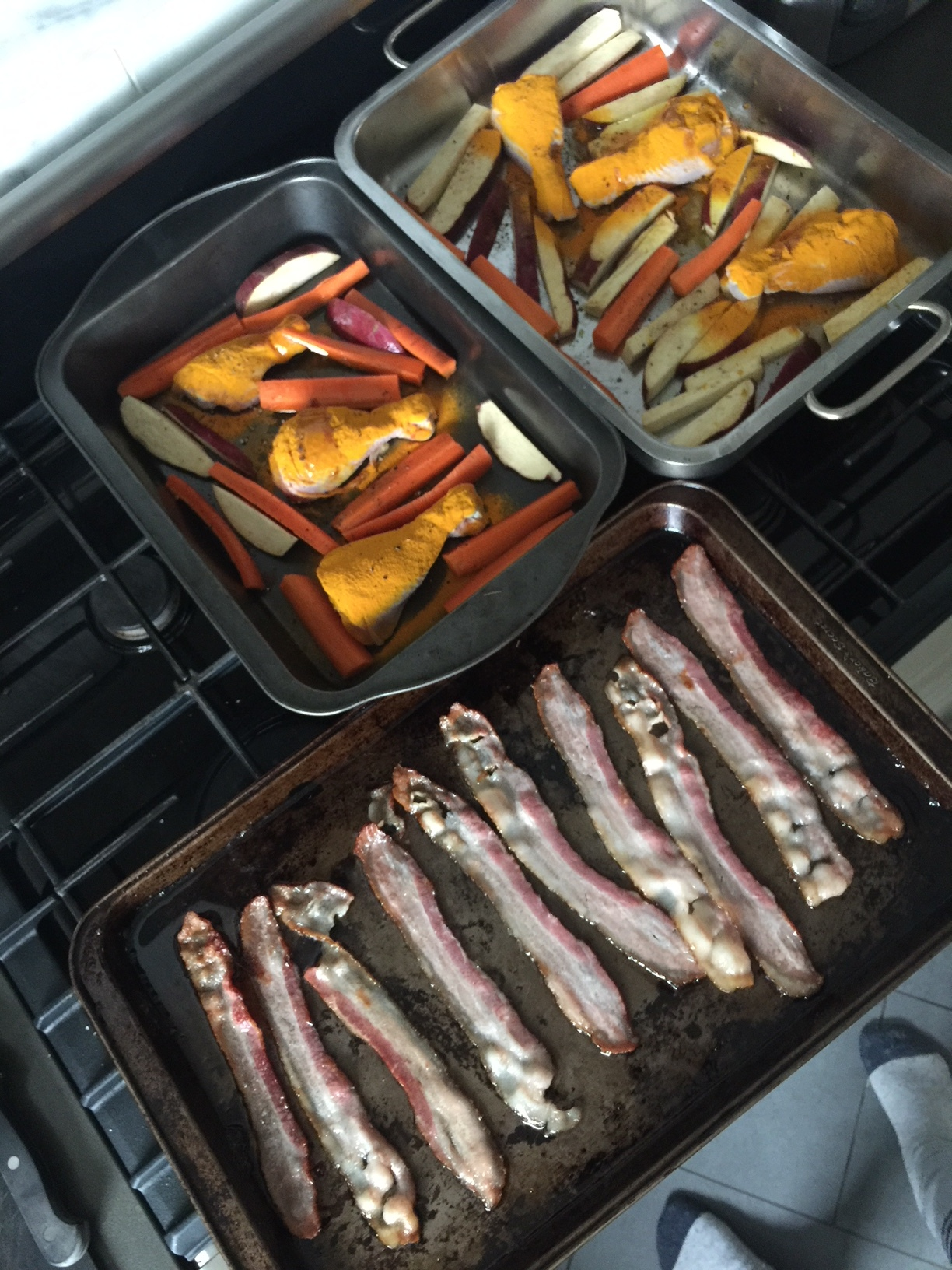 Bacon going in the oven (with two trays of turmeric spiced drumsticks, carrots, and Japanese sweet potato all roasted in bacon fat... um,  HELLO ).