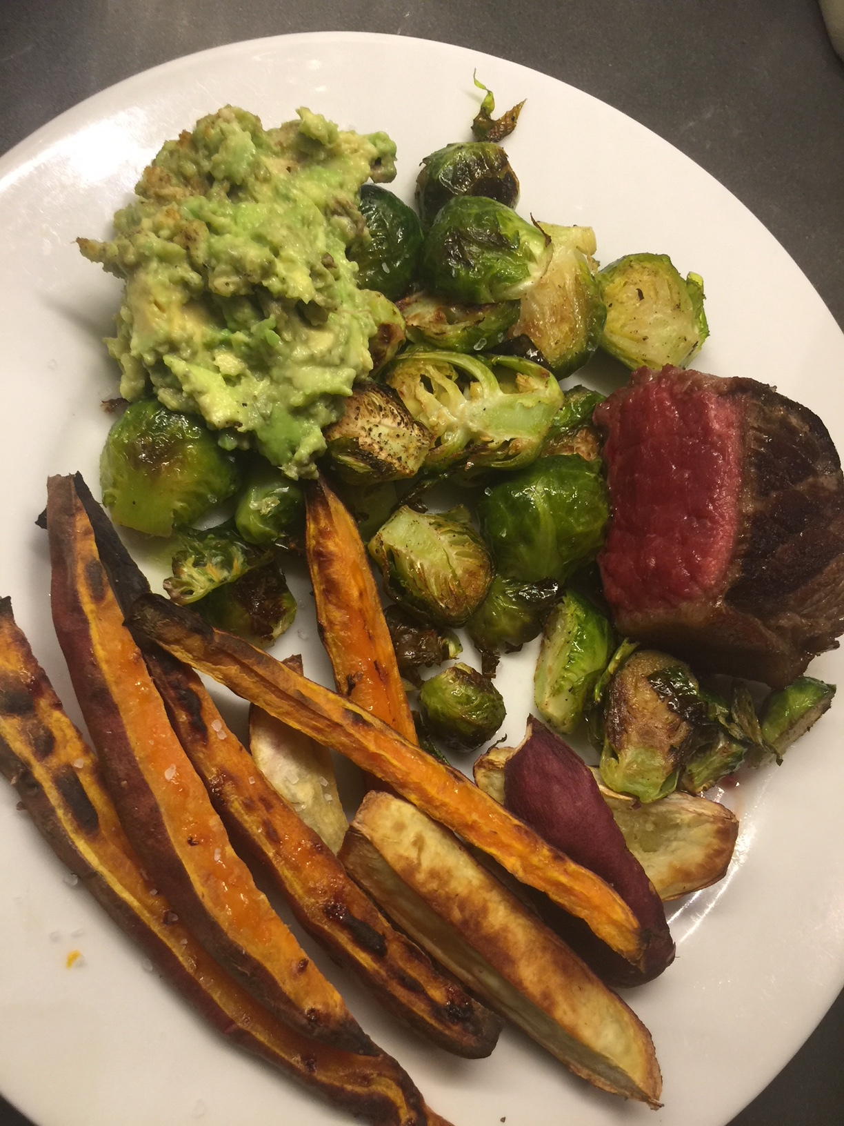 A combo of OG and Japanese sweet potato fries, with brussels, avocado, and  grass-fed beef