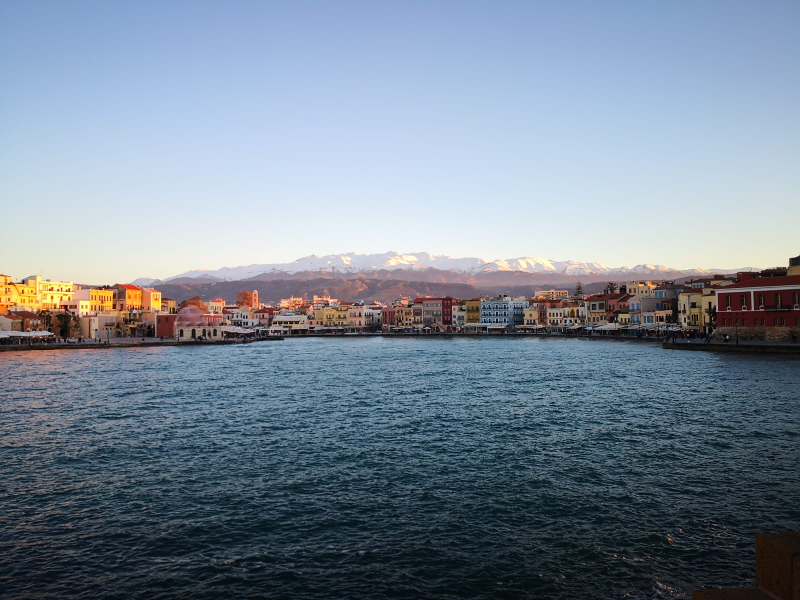 The old Venician Harbour of Chania at sunset, with the white mountains off in the distance.