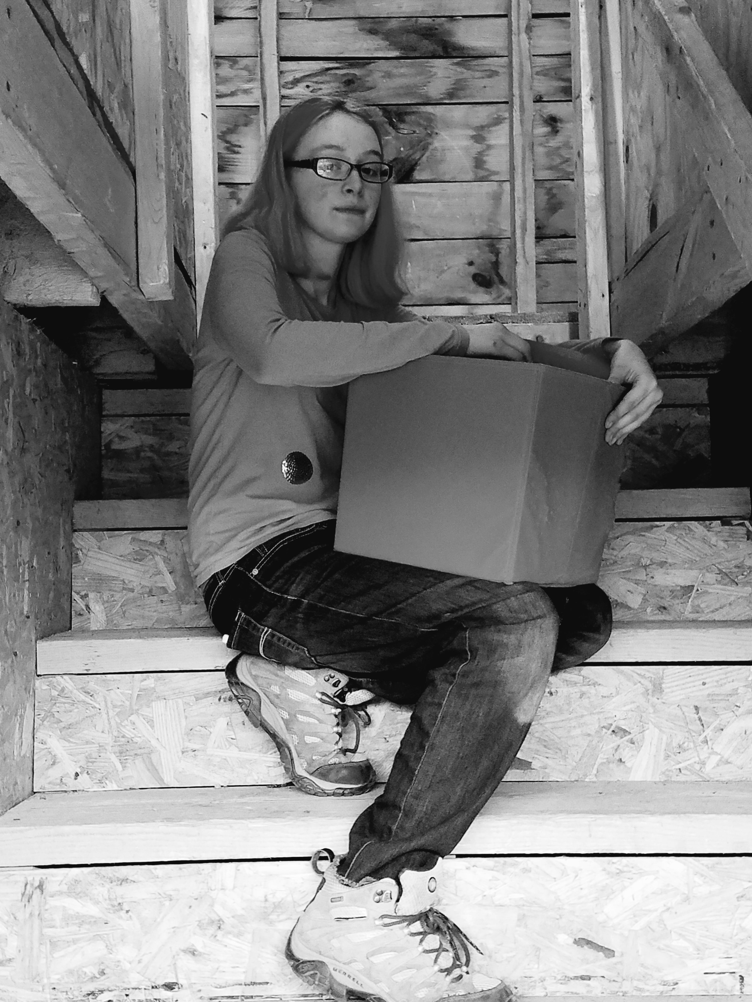Tina's oldest daughter with a box of the family's belongings at their storage unit. (Maine Public photo by Susan Sharon)