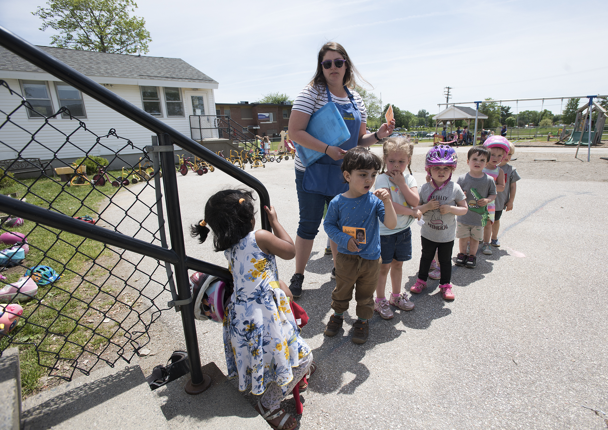 Teacher Ashley Cunningham makes sure all the kids are together before bringing them back inside for lunch at Parkside Children's Learning Center in Bangor in June. (Kevin Bennett photo for Maine Public)