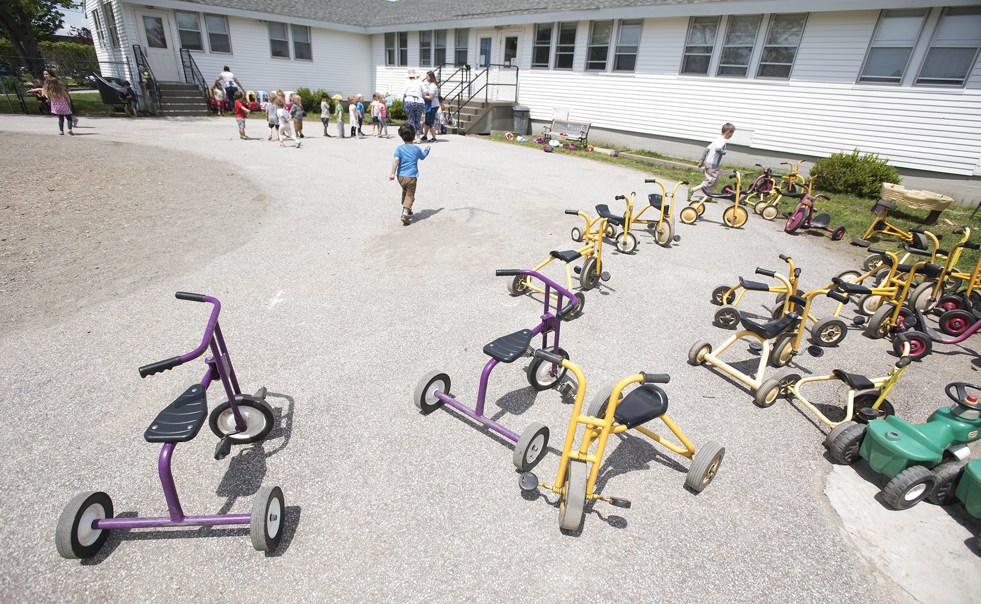 Toys litter the playground as children race to line up for lunch after playing outside at Parkside Children's Learning Center in Bangor in June. (Kevin Bennett photo for Maine Public)