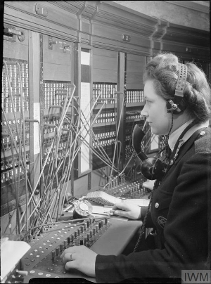 """Credit:  Imperial War Museum . A National Fire Service switchboard operator in action at the NFS London Region headquarters. According to the original caption """"This switchboard is the nerve centre through which the operations officer receives reports of fires and the progress of raiding and through which he issues his orders to the areas where the fire battle is being fought""""."""