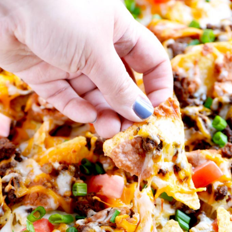 Epic Beef Nachos Supreme - Wow your guests with this Taco Bell inspired recipe! Seasoned ground beef, refried beans, cheese, tomatoes and green onions make such a great flavour combination. This recipe is a winner!Get the Recipe