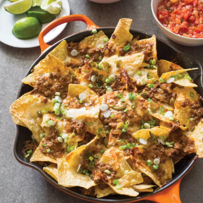 Cast Iron Loaded Beef Nachos - Keep cheese gooey and ground beef zesty! This tasty recipe cooks on the skillet, and transfers to the oven. Creating the ultimate combination of texture and flavour! Topped with onions, garlic, spices, cheese, jalapenos, and scallions. What could be more decadent?Get the Recipe