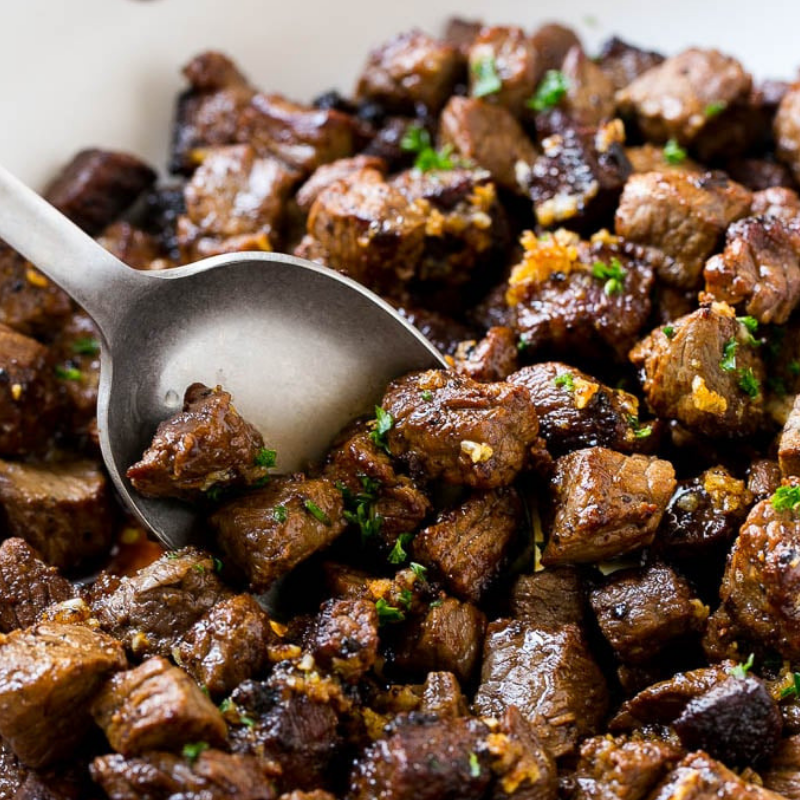 Steak Bites with Garlic Butter - Hearty cubes of lightly seasoned sirloin steak, pan-fried with butter and garlic on high heat for extra crispiness. Delicious and crazy simple! This recipe cooks in less than 5 minutes. Serve on toothpicks as an appetizer, or as a full meal with potatoes and veggies!Get the Recipe