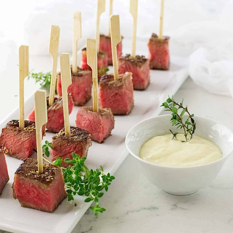 Beef Steak Bites - Juicy, tender, and well-seasoned steak? What more could we ask for? These dynamite bites simmer in butter, garlic, and thyme, all while searing in a hot skillet. Serve these bite-sized cubes with fresh horseradish aioli sauce! Guests will devour them in minutes!Get the Recipe