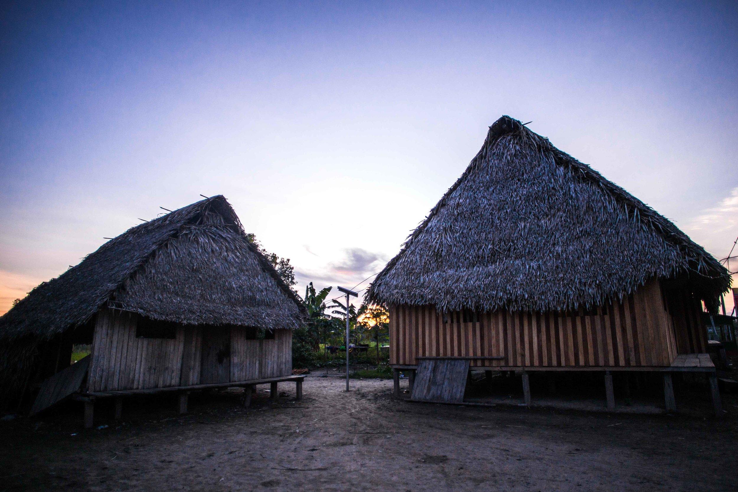La antigua casa de Pekon Rabi a la izquierda, que ahora se usa como su taller y como un espacio para comer al lado de la cocina. La nueva casa ha sido construida con dinero recaudado del proyecto textil y es el espacio para dormir de su extensa familia.