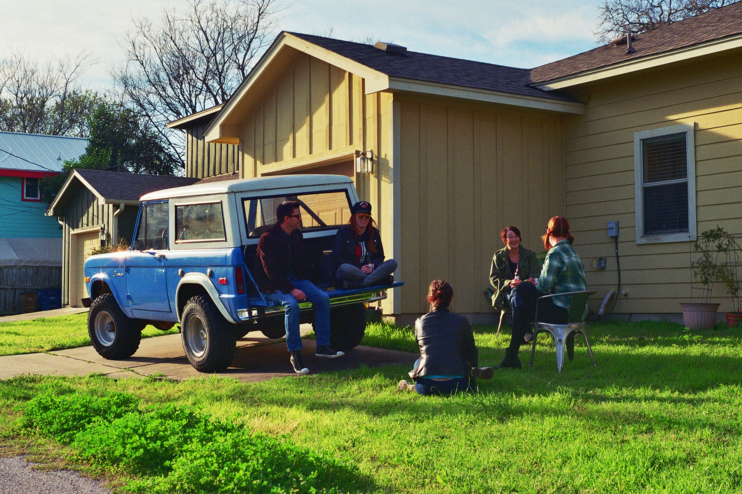 Friends drink beers in the yard over President's Day Weekend.  East Austin, TX