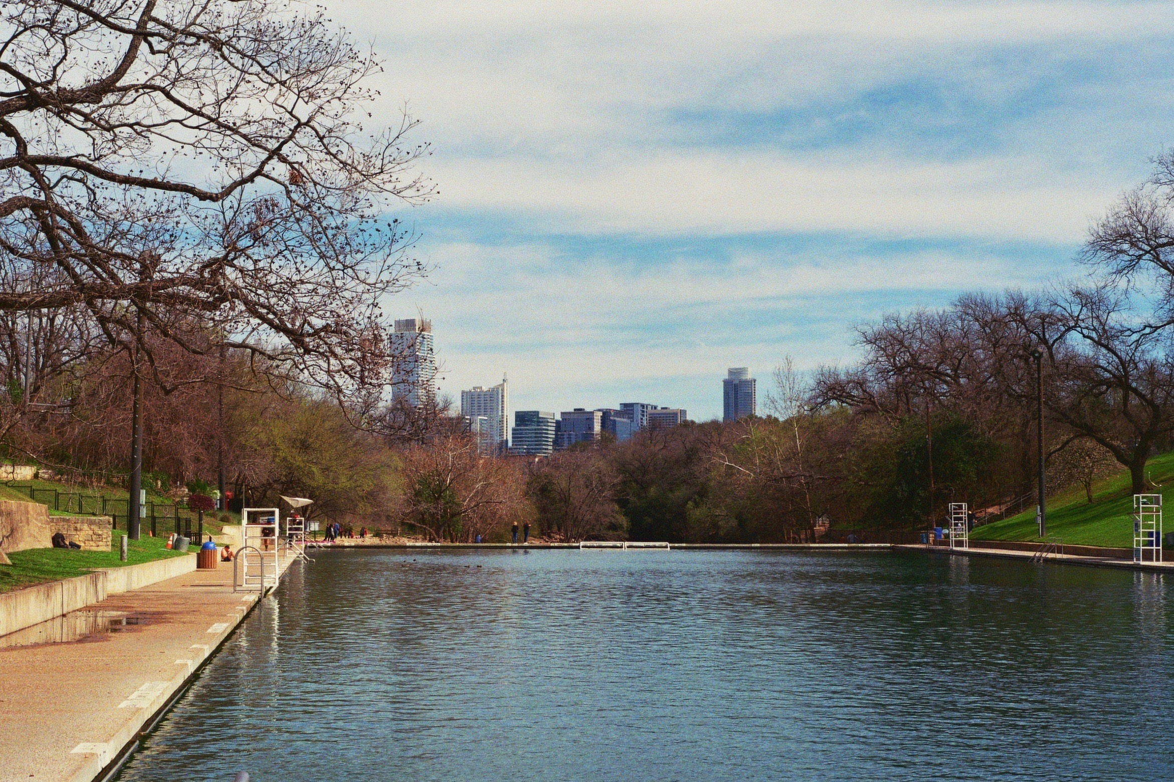 Barton Springs Pool , with the rapidly-growing city skyline off in the distance. Austin, TX