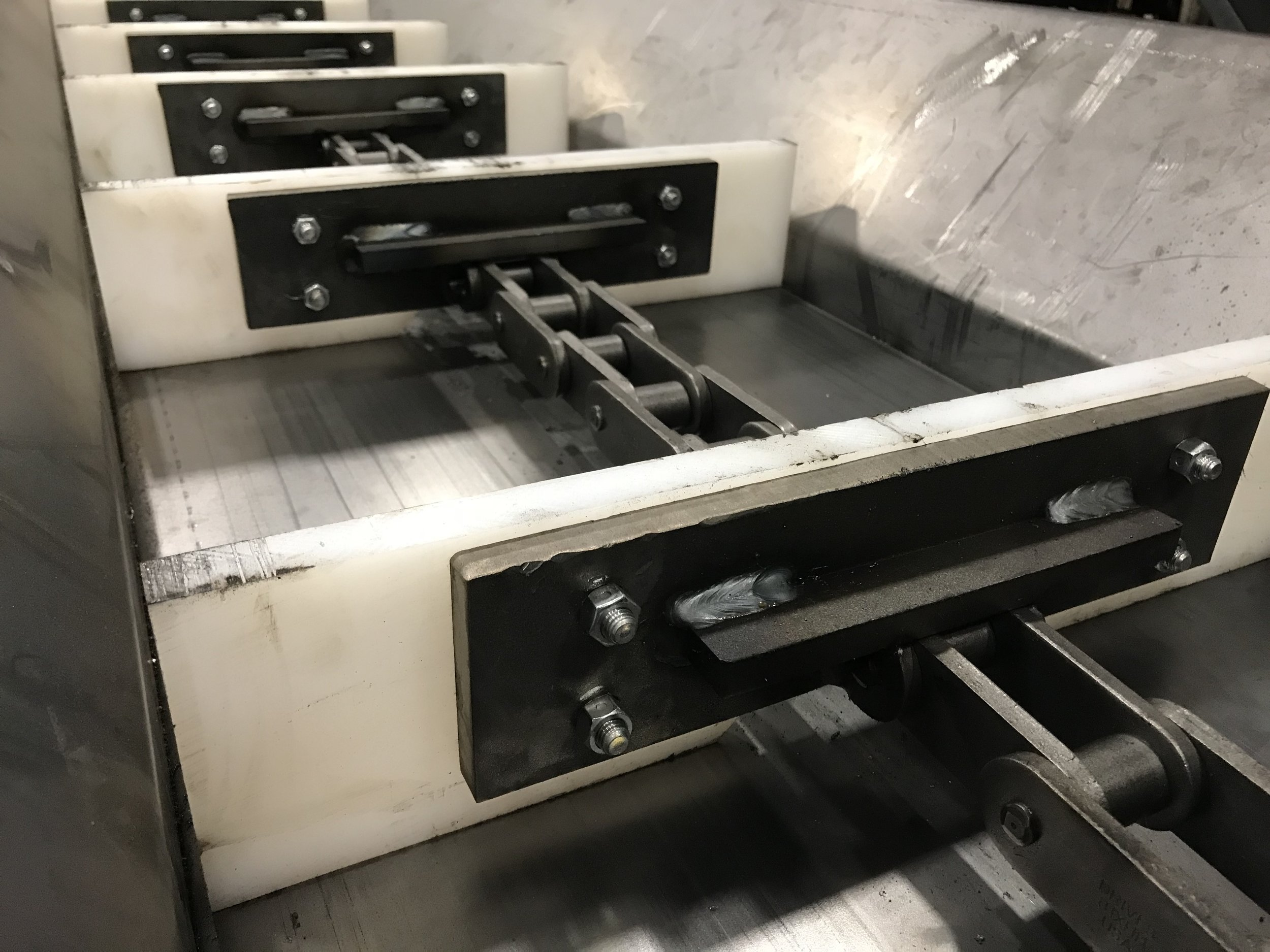 DRAG CHAIN INFEED CONVEYOR   Our heavy duty drag chain conveyor is great for food products that contain liquids or where packaging is fragile. Drag chains are great when the products are too heavy for a cleated belt conveyor.