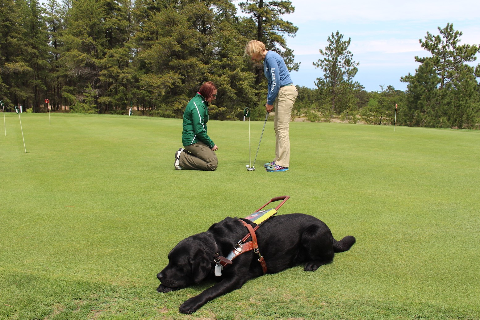 Preston golfing while her Leader dog Floyd enjoys a rest.