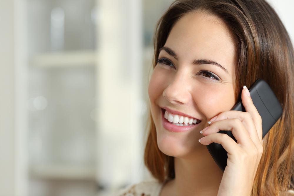 An adult enjoying a successful phone call