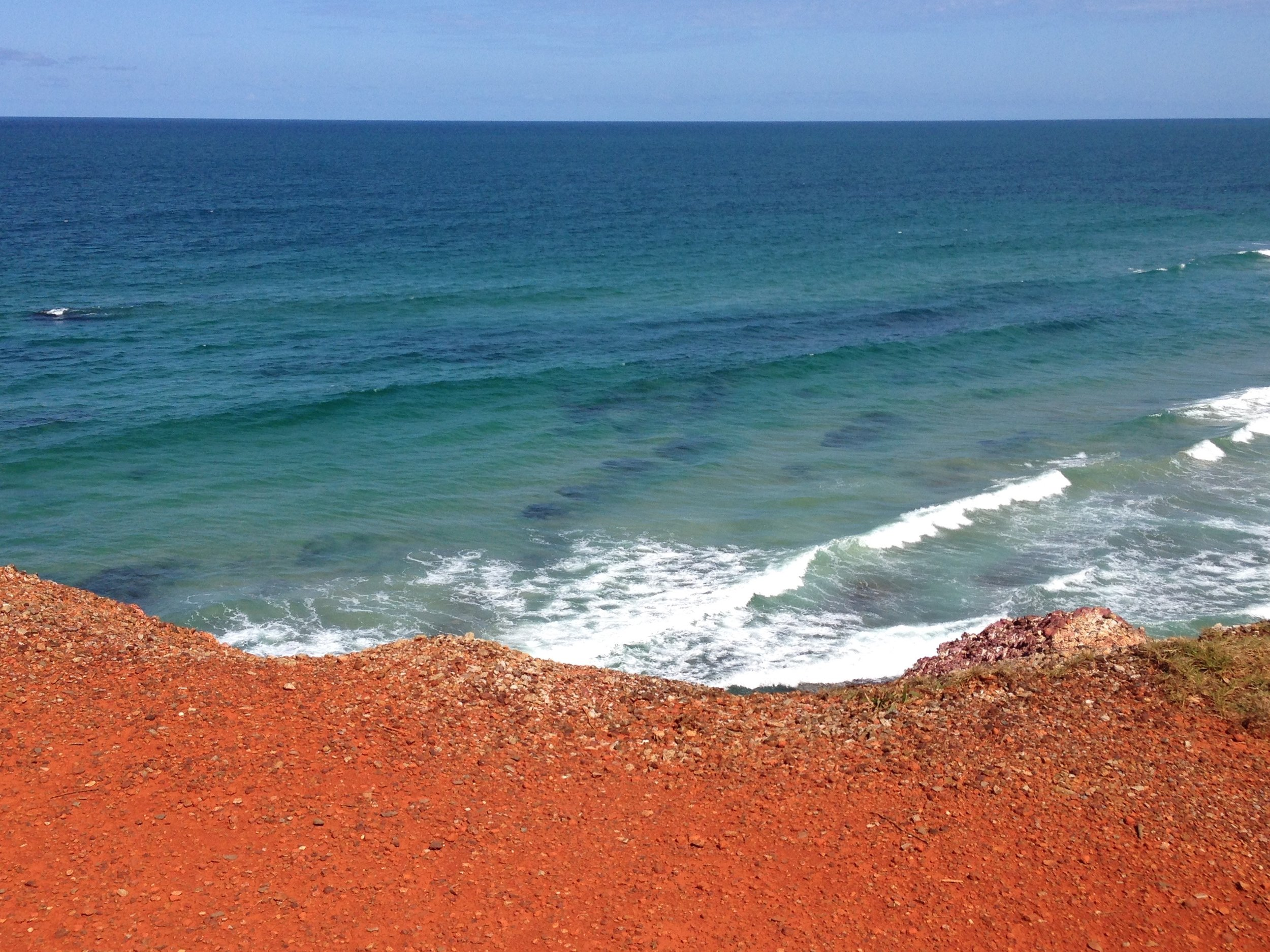 Ochre coloured headland with the turquoise blue sea en route to Minnie Waters