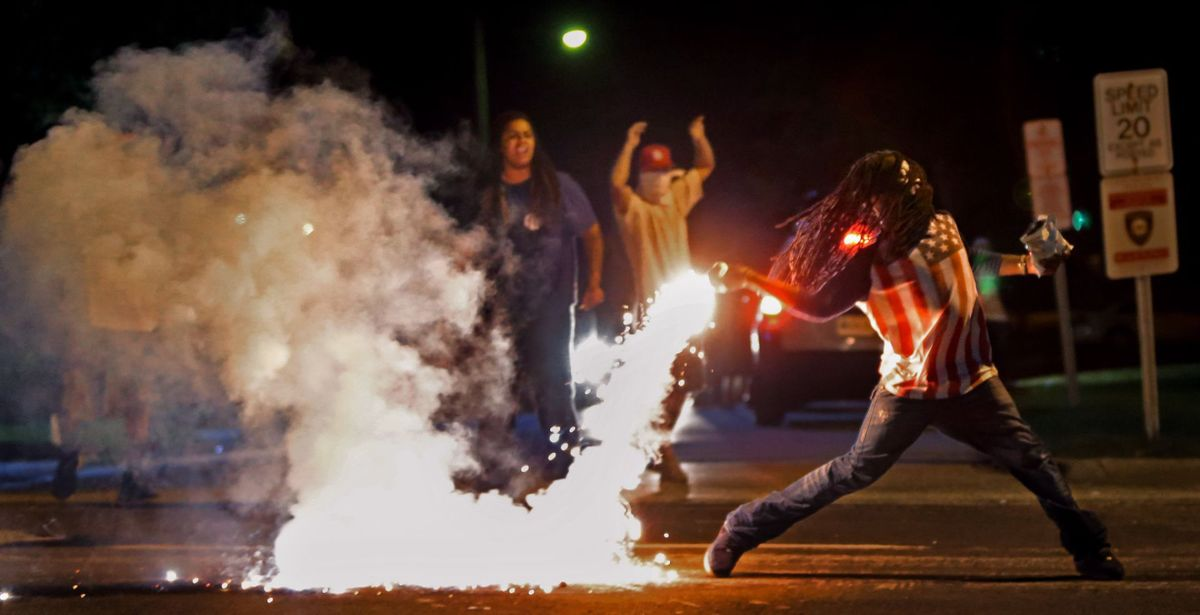 Edward Crawford Jr. throws a container of tear gas back at police officers during a protest against police Aug. 13, 2014, in Ferguson, Mo., four days after a white police officer fatally shot unarmed black teenager Michael Brown. The photo was part of the St. Louis Post-Dispatch's Pulitzer Prize-winning photo coverage of the protests. (Photo: Robert Cohen, St. Louis Post-Dispatch, via AP)