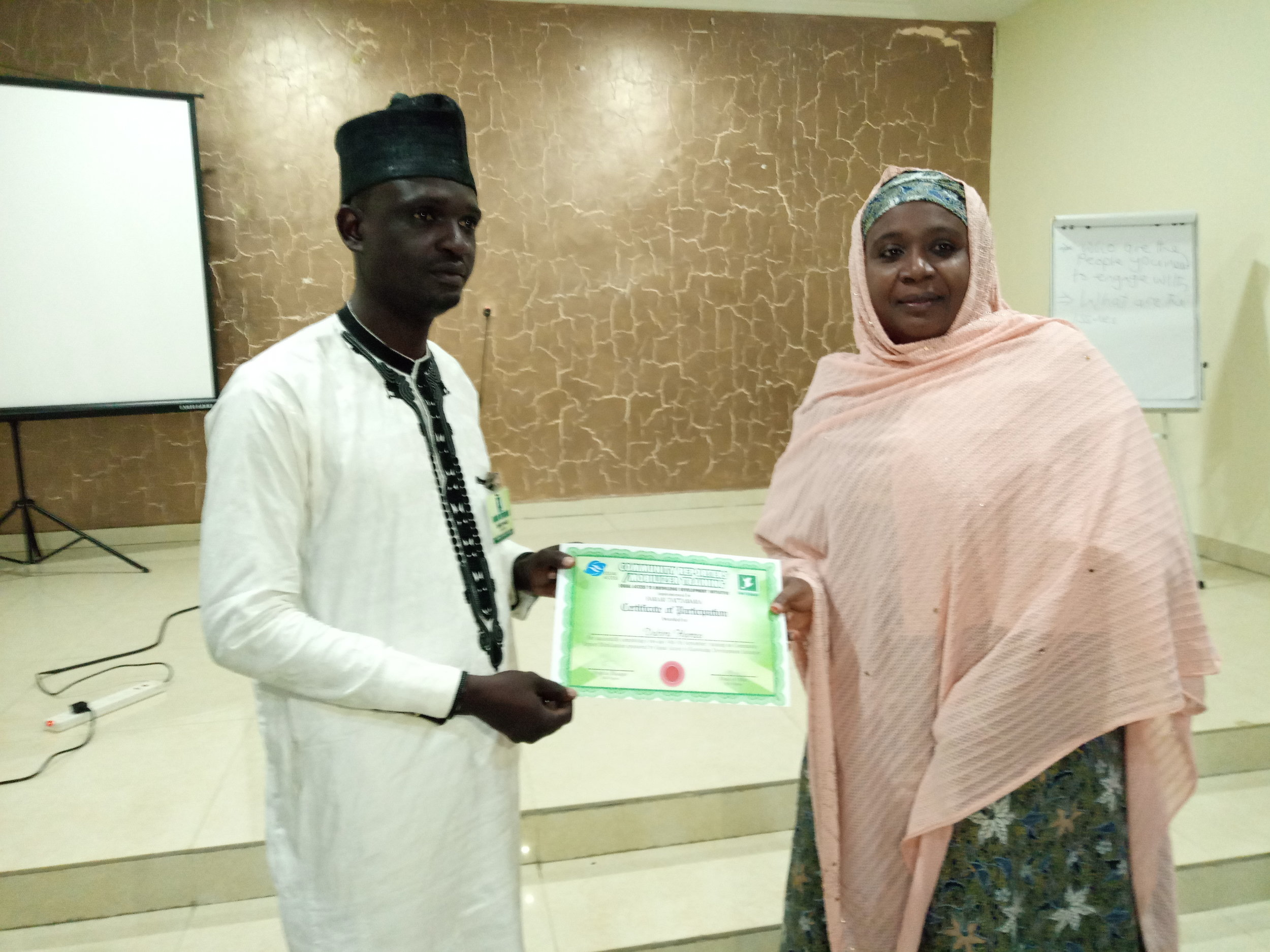 The Head of Office Maryam Muhammad presenting a certificate of completion to Dahiru Hamza from Nasarawa state after the 2-day training.