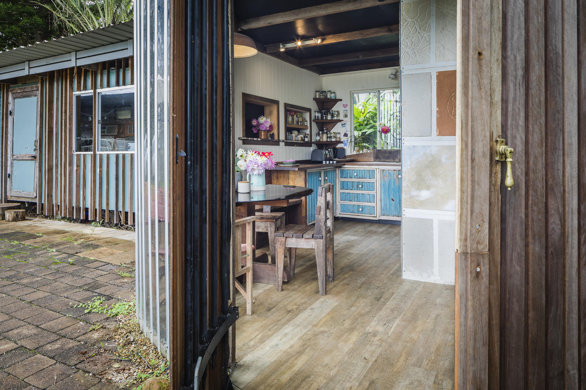 - Across the courtyard is a kitchen and bathroom, formed into a spiral with curved walls built from repurposed warehouse roller doors.Adjoining the kitchen is the original caravan, now the children's bedroom.