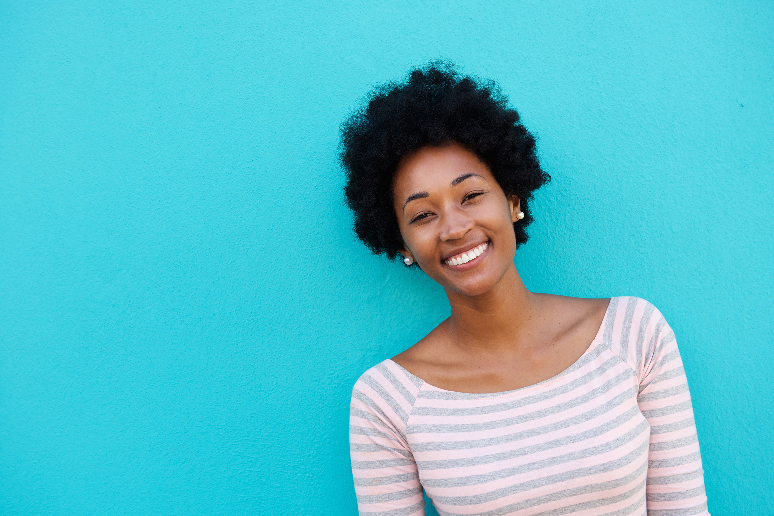 cheerful-woman-standing-against-blue-wall-PBQAALC.png