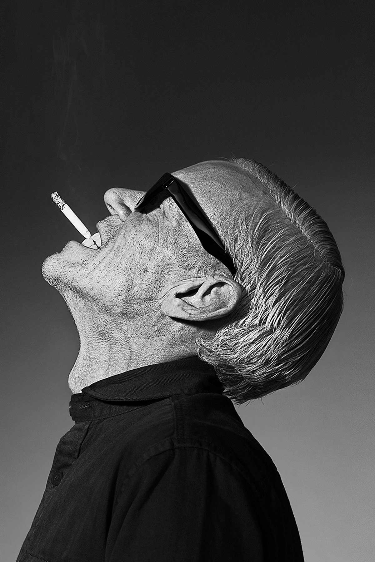 Black and white portrait of mature man with sunglasses and a cigarette. A unique fashion image for Han Kjøbenhavn, who sells apparel for men and women. Photography by Hagedornhagen Copenhagen