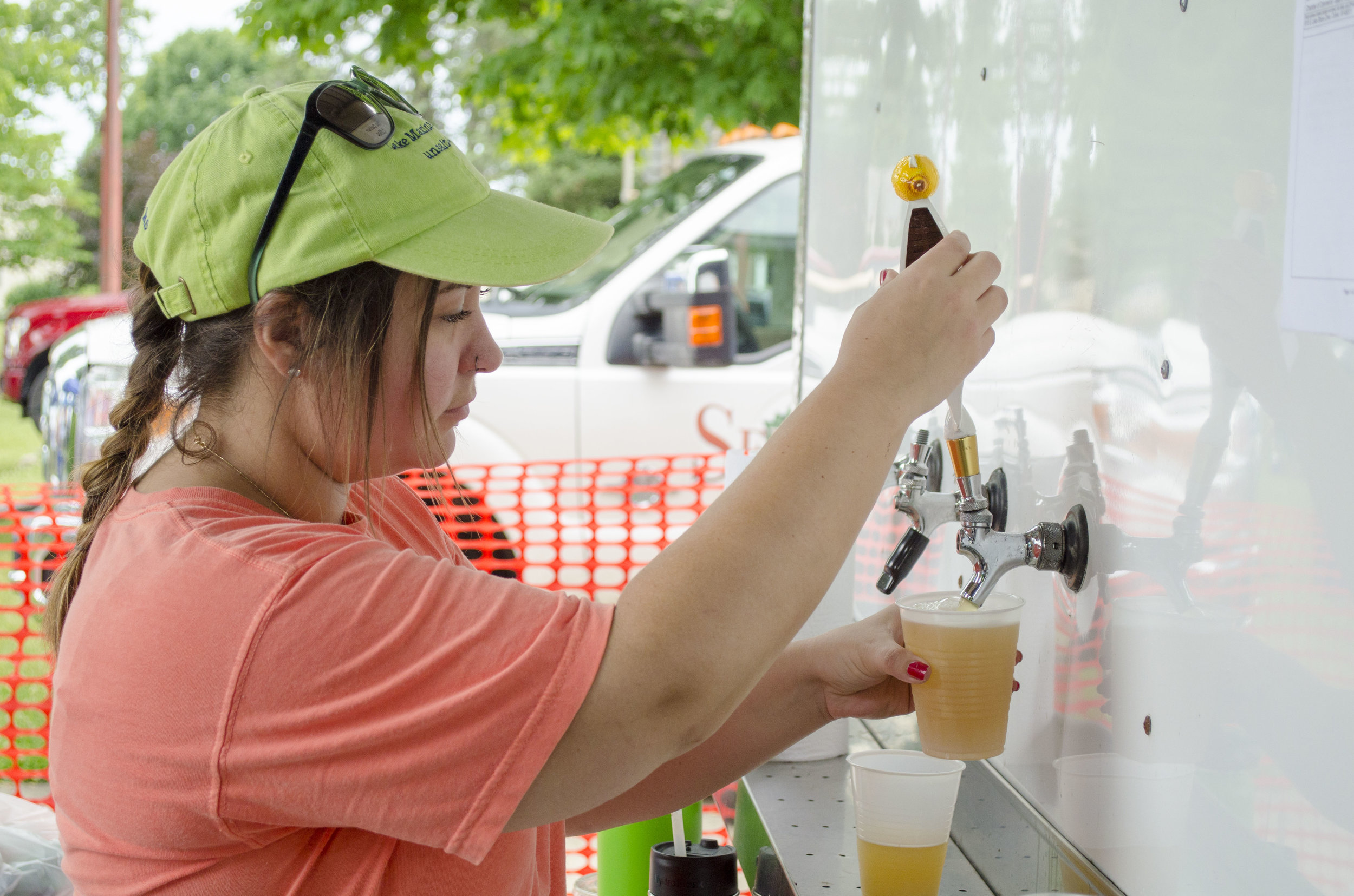 An employee from the Culver Coffee Company pours a beer at their beer garden.