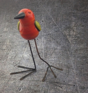 Little flame worked glass bird with steel legs.