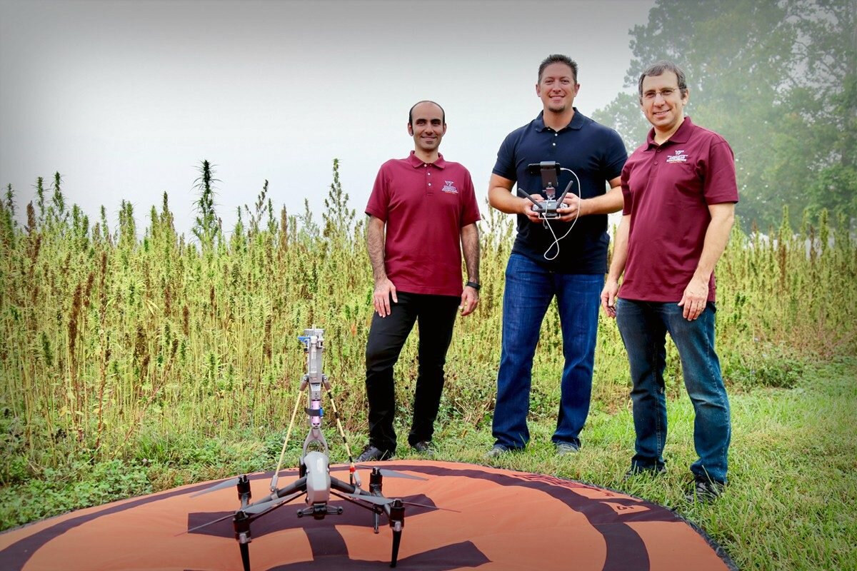 Virginia Tech researchers Hosein Foroutan (left), David Schmale (middle), and Shane Ross (right) standing behind their drone, which is mounted with a 3D-printed sampling device to collect and analyze hemp pollen. (Photo credit: Alex Crookshanks)