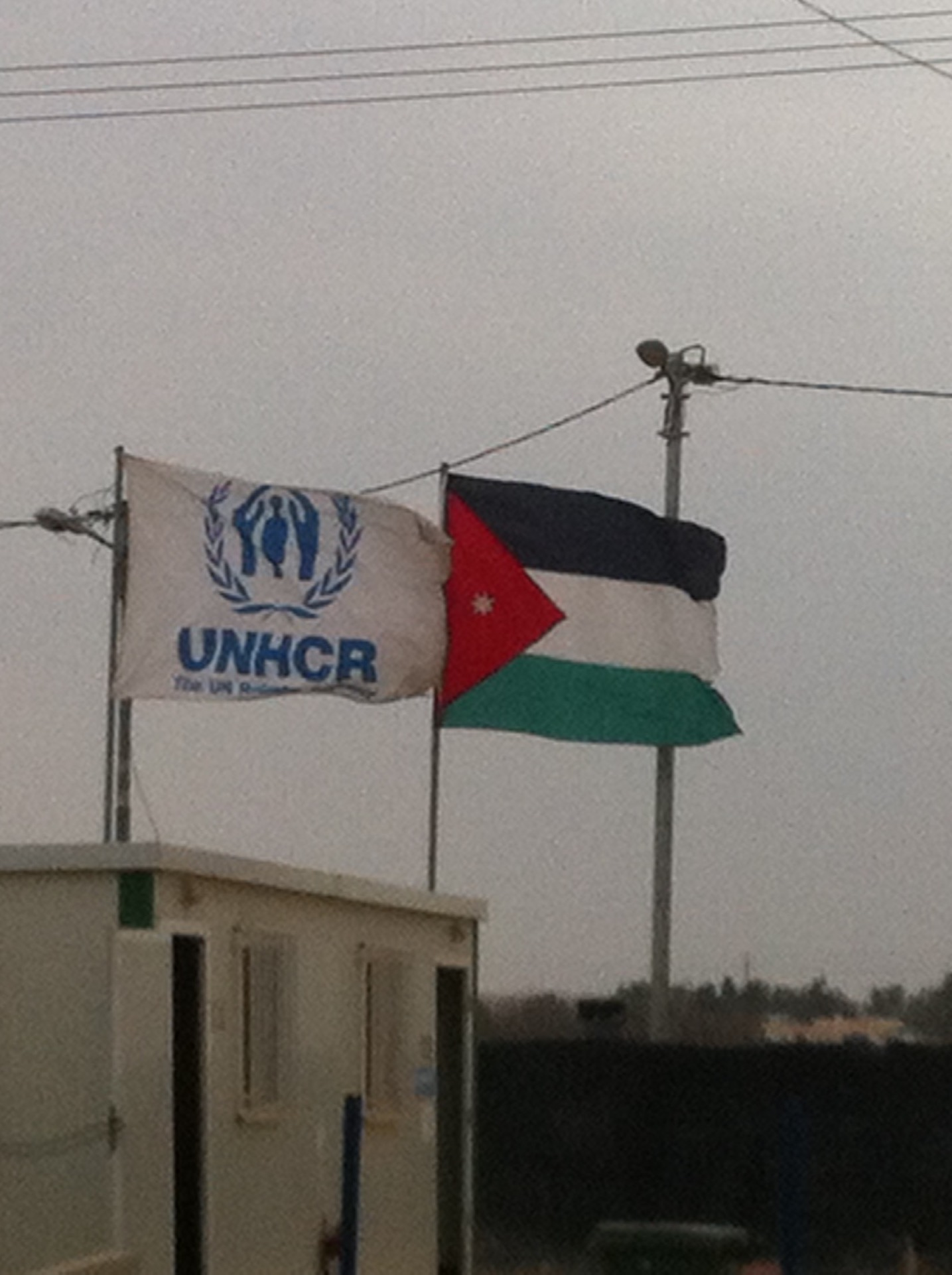 UNHCR and Jordanian flags stand at the entrance to Base Camp, the centre of humanitarian operations in Za'tari, 3 March 2016. Photo by Lewis Turner