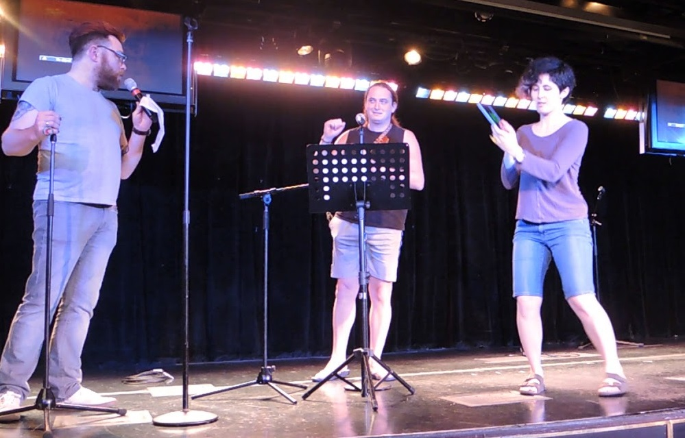 Joey Marianer on stage at the open mic on Joco Cruise 2018, with Travis McElroy and Molly Lewis -