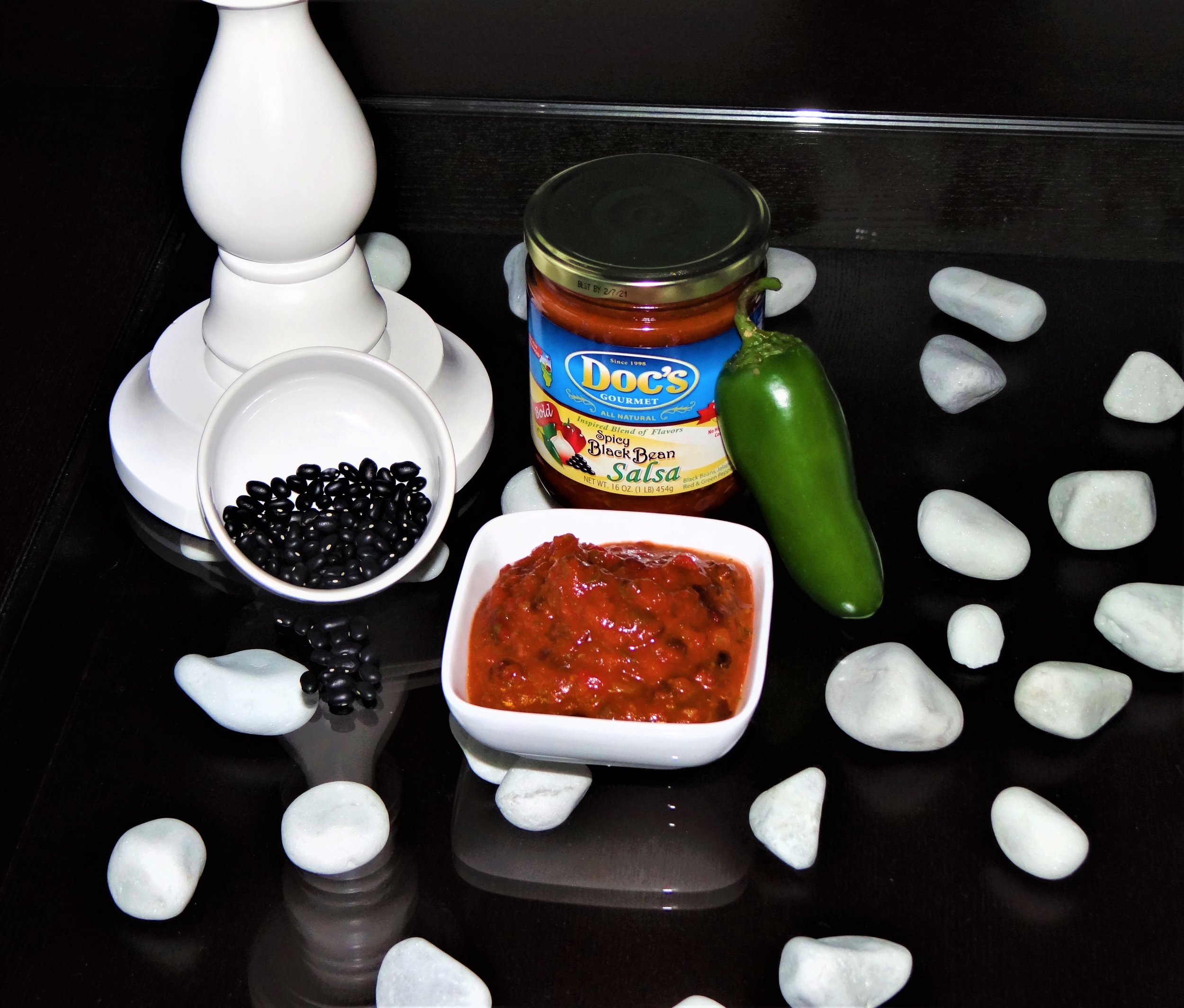 Doc's Spicy Black Bean    Salsa - Doc's Spicy Black Bean Salsa is considered Black Bean Corn's spicy older sister. This salsa is a smoky spice blend of tomatoes and peppers with whole black beans you can see and taste.This special salsa packs just enough heat for any chili, while being modest enough to eat straight out of the jar.