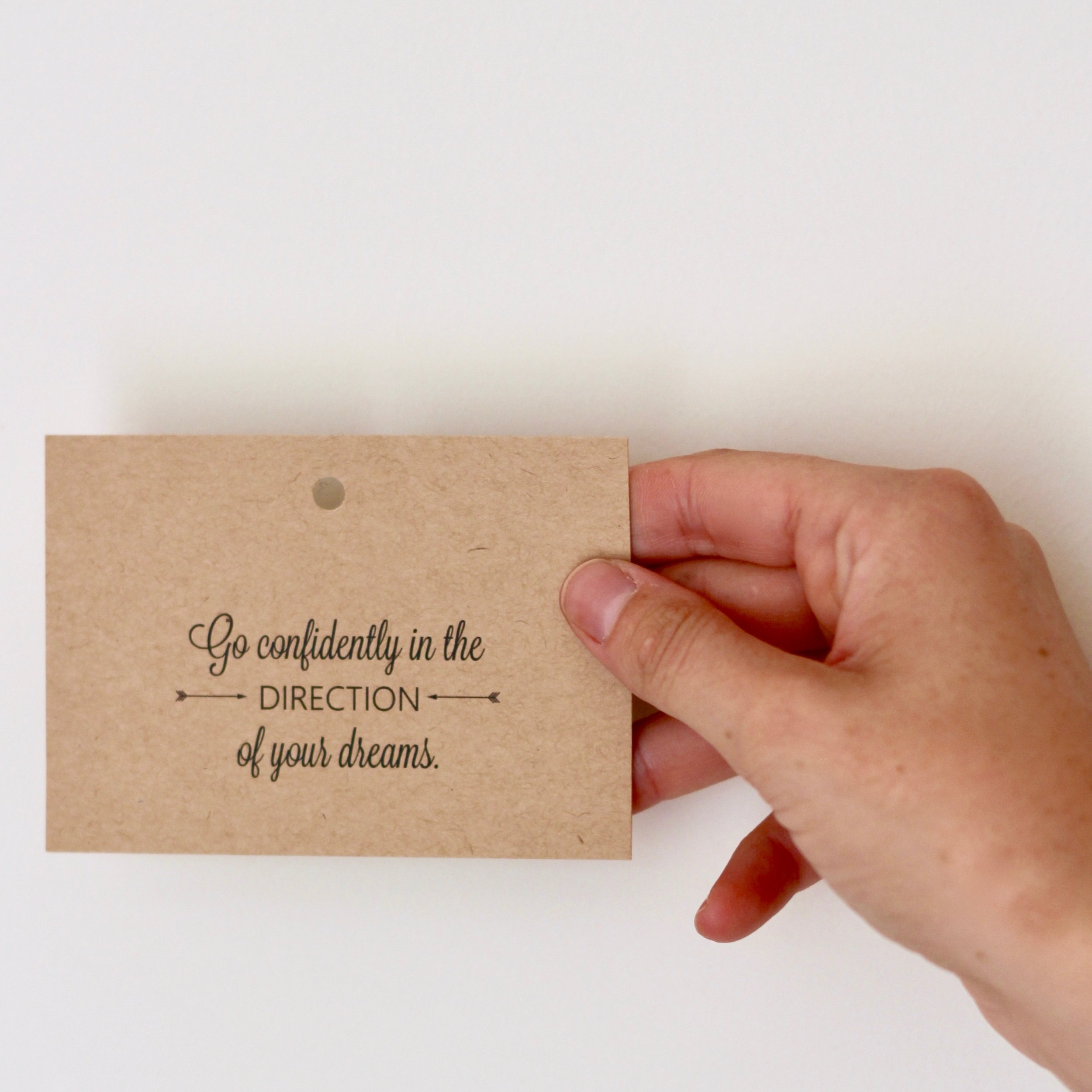 Hand holding card: go confidently in the direction of your dreams