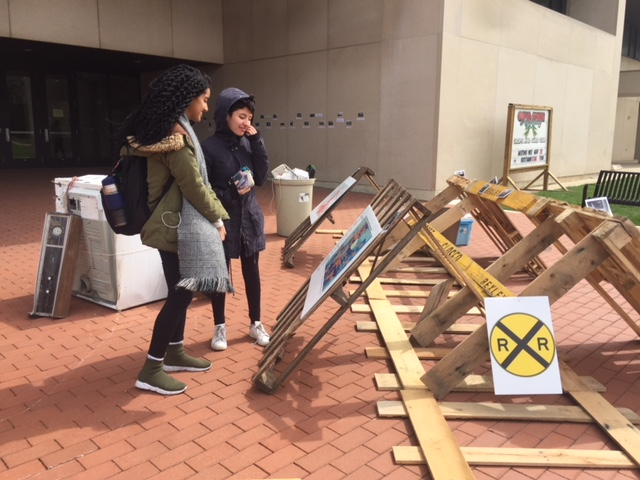 Students examining an interactive art piece in our public art event. This work was created by Katie Brown, Alana Chriest, Eric Swanson, and Tiffany Williams.  The wooden tracks represent the railroad tracks that separate neighborhoods in Columbus. The piece uses demographic maps in Columbus, Ohio to show how these physical barriers are an important part of maintaining racial and economic segregation.